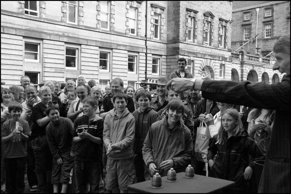 Edinburgh Magician Ian Kendall performing cups and balls on the street in Edinburgh